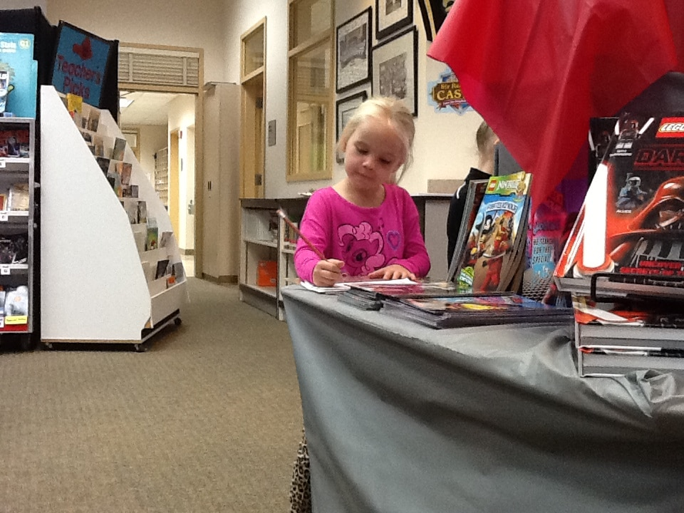Student writing a wish list at the Book Fair